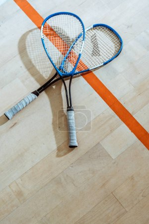 Photo for Two squash rackets on wooden floor in four-walled court - Royalty Free Image