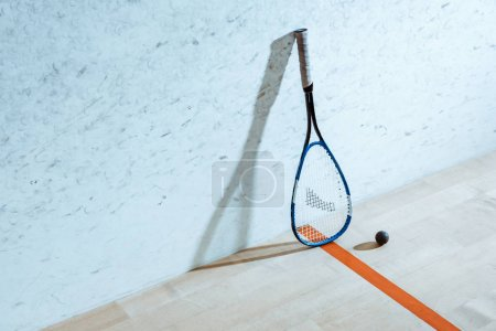 Foto de Raqueta de squash y pelota sobre suelo de madera en cancha de cuatro paredes - Imagen libre de derechos