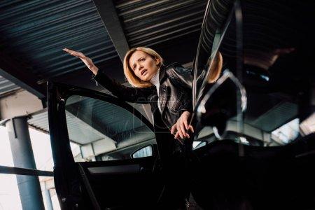 Photo pour Vue basse d'angle de la fille blonde étonnée près de la voiture noire avec la porte ouverte - image libre de droit