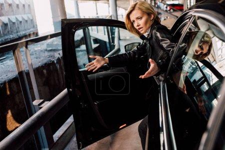 Photo pour Fille blonde émotive faisant des gestes près de la voiture noire avec la porte ouverte - image libre de droit