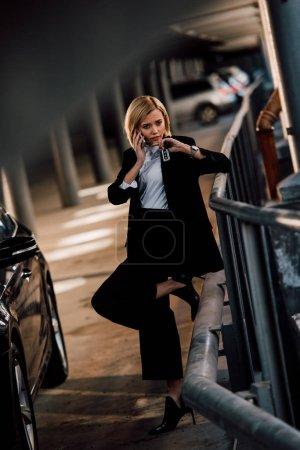 beautiful blonde girl talking on smartphone and holding key near black car