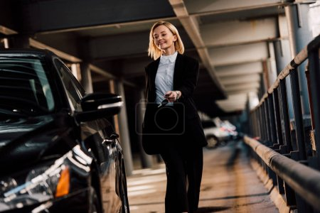 Photo for Cheerful attractive blonde woman walking near black automobile in parking - Royalty Free Image