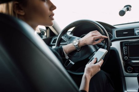 Photo for Cropped view of blonde woman sitting in car and holding smartphone - Royalty Free Image