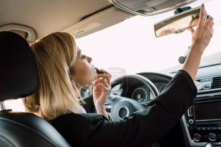 Photo pour Belle fille blonde appliquant rouge à lèvres tout en étant assis dans la voiture - image libre de droit