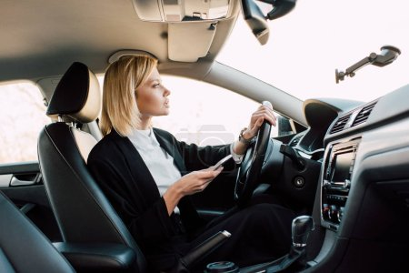 Photo for Attractive blonde young driver holding smartphone while driving car - Royalty Free Image