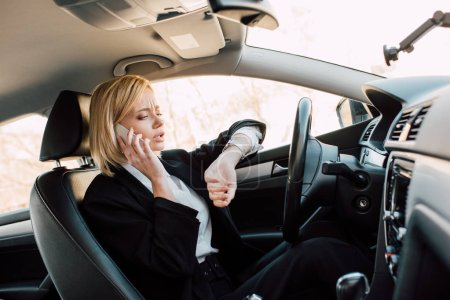 attractive blonde young woman looking at watch while talking on smartphone in car