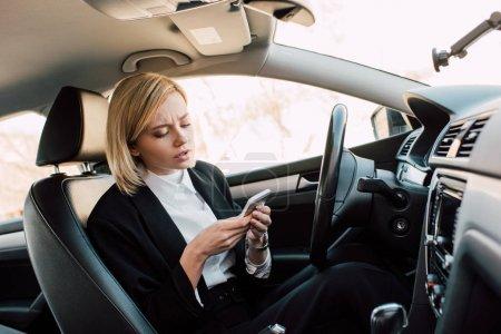 Photo pour Attrayant jeune femme blonde regardant smartphone tout en étant assis dans la voiture - image libre de droit
