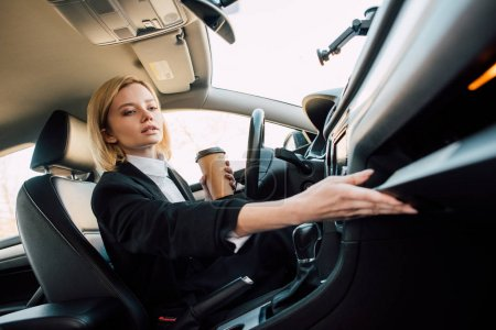 Photo for Low angle view of attractive blonde woman holding coffee to go in car - Royalty Free Image