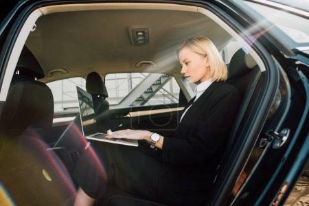 Photo pour Jolie femme blonde en utilisant un ordinateur portable tout en étant assis dans la voiture - image libre de droit