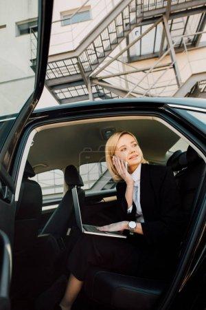 Photo pour Vue à angle bas de la femme souriante parlant sur smartphone tout en étant assis avec un ordinateur portable en voiture - image libre de droit