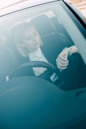 attractive blonde driver looking at watch while holding steering wheel