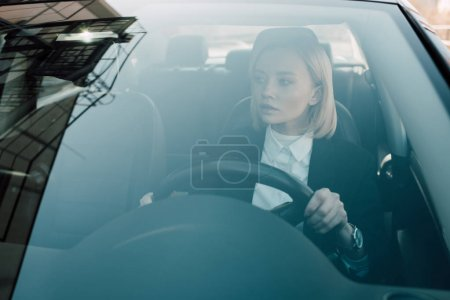 Photo for Pensive blonde driver holding steering wheel while driving car - Royalty Free Image