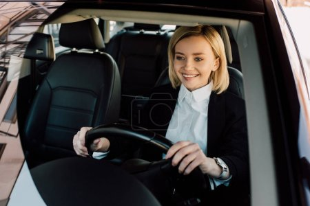 Photo for Cheerful blonde driver holding steering wheel while driving car - Royalty Free Image
