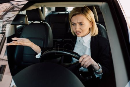 Photo for Upset blonde girl holding steering wheel while gesturing and driving car - Royalty Free Image