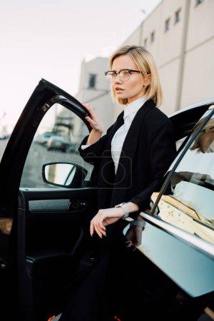 schöne blonde junge Frau mit Brille, die neben schwarzem Auto steht