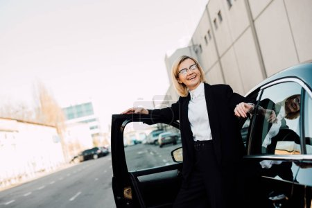 Photo for Happy blonde young woman in glasses standing near black automobile in parking - Royalty Free Image