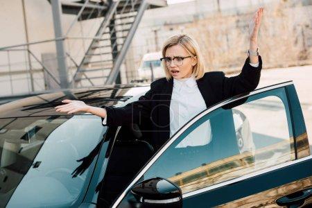 Photo pour Frustré jeune femme gestuelle près de voiture noire dans le parking - image libre de droit