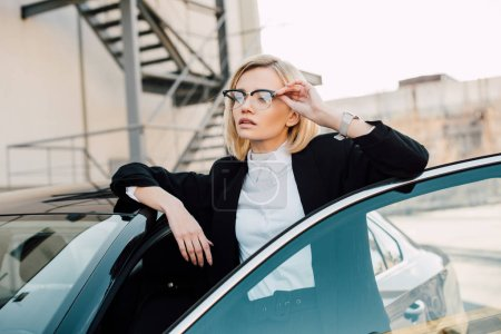 Photo for Confident blonde young woman in glasses standing near black automobile and touching glasses - Royalty Free Image