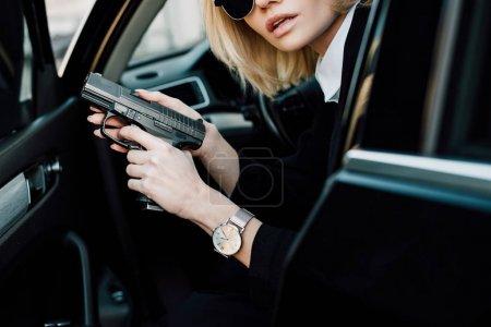 Photo pour Vue recadrée de femme blonde sérieuse retenant le pistolet dans la voiture - image libre de droit