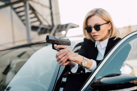 Photo pour Foyer sélectif de la femme blonde sérieuse dans le pistolet de fixation de lunettes de soleil près de la voiture noire - image libre de droit