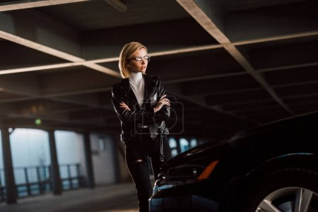 hübsche junge blonde Frau mit Brille, die mit verschränkten Armen neben Auto steht