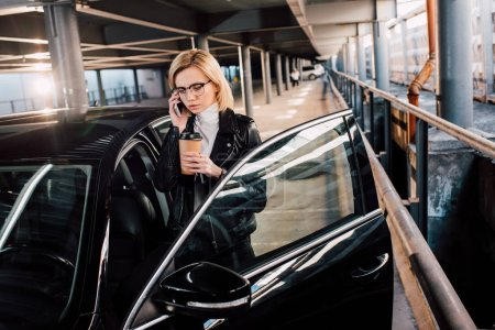 serious girl in glasses talking on smartphone and holding coffee to go near black car