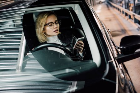 Photo for Blonde attractive woman looking at smartphone while holding steering wheel in car - Royalty Free Image