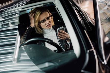 emotional girl in glasses looking at smartphone in car