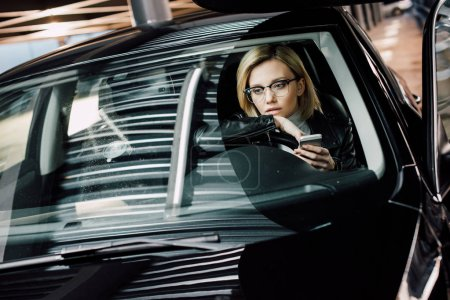 Photo pour Bouleversé fille blonde dans des lunettes tenant smartphone dans la voiture - image libre de droit