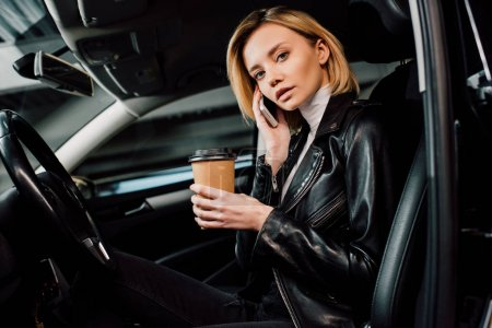 Photo for Blonde girl holding paper cup and talking on smartphone in automobile - Royalty Free Image