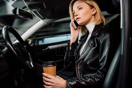 Photo for Dreamy blonde girl holding paper cup and talking on smartphone in car - Royalty Free Image