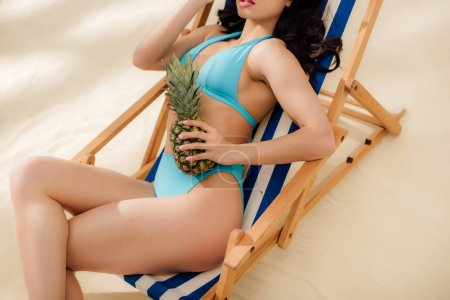 Photo for Cropped view of girl in bikini holding pineapple and relaxing on deck chair on beach - Royalty Free Image