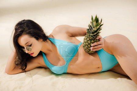Foto de Sexy girl in blue Bikini and sunglasses posing with pineapple while lying on sandy beach - Imagen libre de derechos