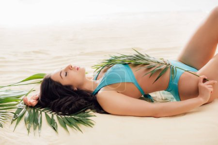 Photo for Attractive sexy Young woman in bikini posing with green leaves while relaxing on beach - Royalty Free Image