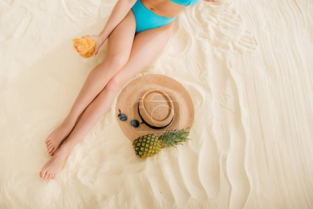 Photo for Top view of girl in bikini with cocktail, Straw Hat, Pineapple and sunglasses relaxing on beach - Royalty Free Image
