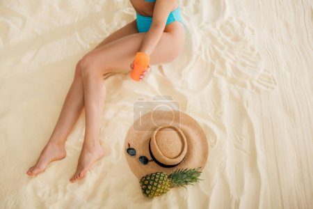Photo for Top view of girl in bikini with sunscreen, Straw Hat, Pineapple and sunglasses relaxing on beach - Royalty Free Image