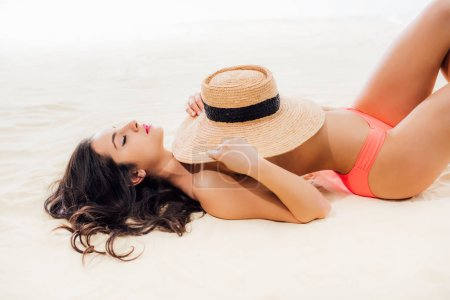 Photo for Beautiful sexy girl covering breasts with straw hat while lying on beach - Royalty Free Image