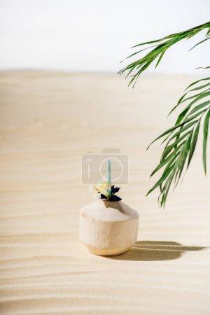 Photo pour Cocktail de noix de coco avec la fleur et les feuilles de palmier sur la plage - image libre de droit