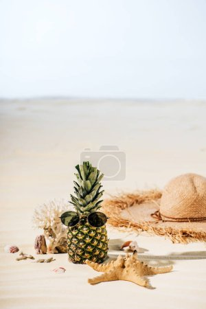 Photo for Pineapple with sunglasses, starfish, Straw Hat and sea stones on beach with copy space - Royalty Free Image