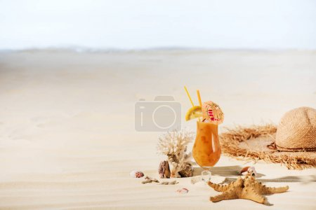 Photo for Cocktail, starfish, Straw Hat, coral and sea stones on sandy beach with copy space - Royalty Free Image