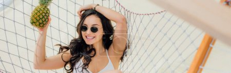Photo for Panoramic shot of beautiful smiling girl in sunglasses holding pineapple and lying in hammock on beach - Royalty Free Image