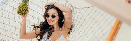 Photo pour Plan panoramique de belle fille souriante dans des lunettes de soleil tenant l'ananas et couché dans un hamac sur la plage - image libre de droit