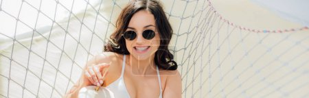 Photo pour Plan panoramique de belle fille souriante dans des lunettes de soleil avec cocktail de noix de coco couché dans un hamac sur la plage - image libre de droit