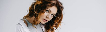 Foto de Panoramic shot of pretty girl with red hair looking at camera on white - Imagen libre de derechos