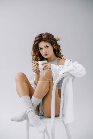 Photo for Beautiful woman looking at camera and holding cup on grey - Royalty Free Image