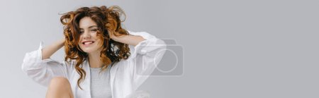 Photo for Panoramic shot of cheerful girl touching red curly hair and smiling on grey - Royalty Free Image