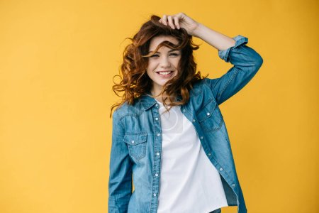 Photo for Pretty young cheerful woman touching hair and smiling on orange - Royalty Free Image