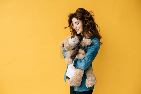 Photo for Cheerful curly young woman holding teddy bear on orange - Royalty Free Image