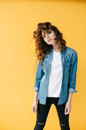 Photo for Attractive curly redhead girl posing and looking at camera on orange - Royalty Free Image