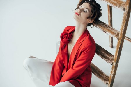 Photo for Overhead view of stylish young woman sitting near wooden ladder with closed eyes on white - Royalty Free Image